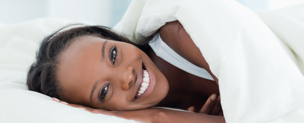 Radiant woman waking up with good skin and smile